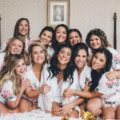 Bridal party smiling in robes on bed